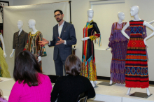 Image of the Director of the Onstead Institute speaking to a group of workshop participants with six mannequins in background wearing bright colored dresses