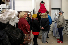 Group of six workshop participants touring the Texas Fashion Collection facility, standing around mannequins that are wearing various styles and colors of dresses.