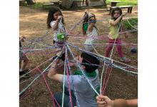 Campers creating a community ball together with yarn