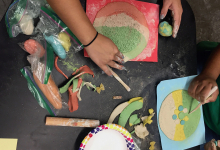 Close-up image of two workshop participant's ceramics projects, with hands holding paintbrushes and a variety of art supplies scattered across table.