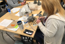 Image of two ceramics workshop participants sitting at table and working on their projects. Assorted supplies scattered across table, including clay, sculpting tools, and sketches.