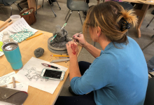 Image of ceramics workshop participant sitting at table and working on sculpture. Sketches of projects and clay supplies scattered across table.