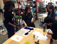 Image showing five workshop participants working on individual printmaking projects in a large classroom with a variety of supplies in the background.