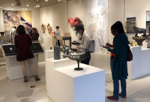 Group of workshop participants touring an art gallery and taking notes as they view the displays and sculptures.