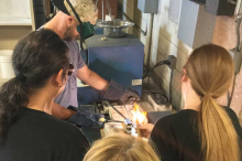 Image of workshop facilitator with protective eye equipment performing a metal casting demonstration with several workshop participants gathered around table.