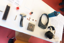 Assorted metal working supplies scattered across table, including a hammer, metal medallions, goggles, and headphones.
