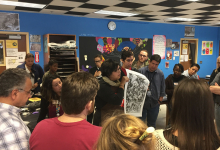 Image of a large group of workshop participants standing around the workshop facilitator and listening to an instructional session on printmaking. Workshop facilitator is holding up a sample of a printmaking project.