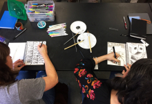 Two workshop participants using markers and paintbrushes to sketch in a journal. Assorted supplies scattered across table, including markers and paint supplies.