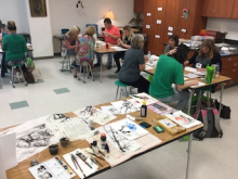 Image of large classroom with nine workshop participants sitting at group tables and working on ink painting projects. Large supply table shown at front of image, with various ink painting supplies scattered across table.